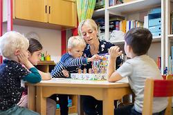 Auf diesem Bild ist eine Erzieherin mit einigen Kindern beim Spielen an einem Tisch zu sehen.