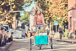 Auf diesem Bild ist eine Frau auf einem Lastenrad zu sehen.