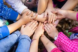 Auf diesem Bild ist ein Handkreis aus Kinderhänden zu sehen.