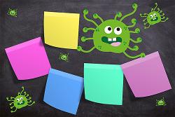 Auf diesem Bild ist eine Grafik von Coronaviren mit Gesichtern auf einer Tafel mit verschiedenfarbigen Post-its zu sehen.