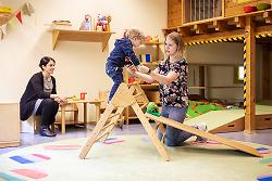 Auf diesem Bild sind zwei pädagogische Fachkräfte mit einem spielenden Kind in einer der städtischen Kitas zu sehen.