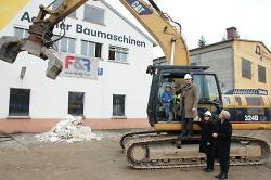 Oberbürgermeister Thilo Rentschler, Erste Bürgermeisterin Jutta Heim-Wenzler und Ortsvorsteherin Andrea Hatam beim ersten Baggerbiss