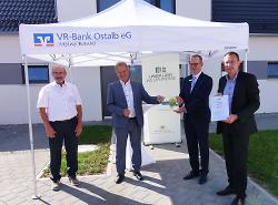 Umweltminister Franz Untersteller (2.v.li.) überreichte an VR-Bank-Chef Kurt Abele die Auszeichnung. OB Thilo Rentschler (re.) und Hans-Peter Weber (li.) freuen sich über die Fertigstellung der Häuser.