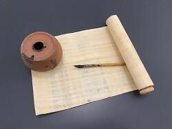 Auf diesem Bild sind eine Papyrusrolle, ein Ton-Tintenfass und eine Schreibfeder zu sehen.