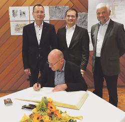 Verkehrsminister Winfried Hermann trägt sich in das Goldene Buch der Stadt Aalen ein, hinten rechts Regierungspräsident Wolfgang Reimer