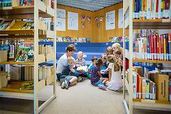 Auf diesem Bild sind zwei Erzieherinnen und eine Gruppe Kinder in einer Bibliothek beim Lesen zu sehen.