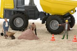 Auf diesem Bild ist im Hintergrund ein Spielzeug-Lastwagen zu sehen, davor stehen kleine Figuren. Ganz links ist ein Männchen mit Schaufel und Schubkarre, in der Mitte eines mit Spitzhacke und rechts eines mit gelbem Helm, der Anweisungen auf der Baustelle gibt. Dazwischen stehen kleine orangene Pylonen.
