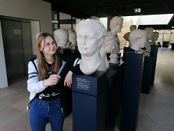 Auf diesem Bild ist die Schülerin Victoria Straub mit einem Mikrofon und der Büste von Kaiser Domitian zu sehen.