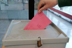 Aus diesem Bild ist zu sehen, wie eine Hand einen roten Wahlbrief in eine Wahlurne im Aalener Rathaus steckt.