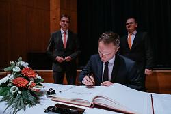 Hier trägt sich Frederick Brütting in das Goldene Buch der Stadt Aalen ein. Im Hintergrund stehen Wolfgang Steidle und Dr. Joachim Bläse